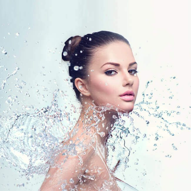 Beneficial effects - An image whit a girl whit flawless skin splashed by water on her upper body.